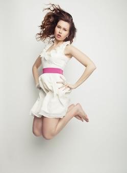 Очаровательная женщина в белом платье, перепрыгивая через серую стену