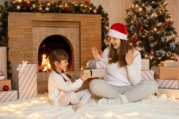 Очаровательный ребенок женского пола представляет рождественский подарок своей матери в рождественское утро