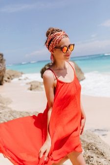 Charming female model in red dress walking down the ocean coast. outdoor shot of enthusiastic young woman wears sunglasses during rest near sea.