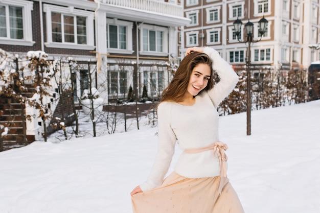 Affascinante modello femminile in maglione e gonna rosa che balla in cortile nella mattina d'inverno. foto all'aperto di splendida donna che gode della prima neve nel giorno di dicembre.