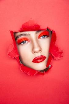 Очаровательная женская модель с красным макияжем, глядя сквозь рваную бумагу в студии