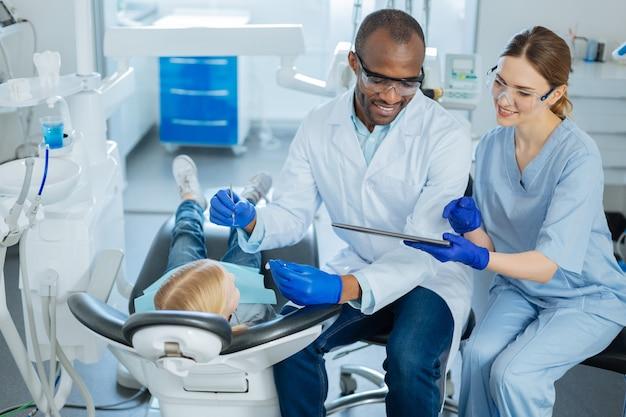 小さな女の子の虫歯を調べている間、歯科医にタブレットで重要なメッセージを示す魅力的な女性看護師