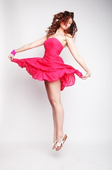 Charming female in pink dress jumping