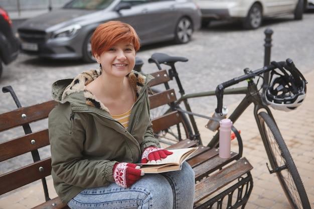 매력적인 여학생이 도시에서 책을 읽고, 자전거를 타고 쉬고 있습니다.