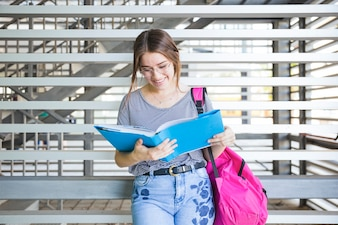 Charming female student reading book