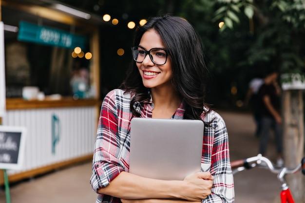 通りに立っているウェーブのかかった髪の魅力的な女子学生。ノートパソコンを持って周りを見回している市松模様のシャツを着たかなり日焼けした女の子。