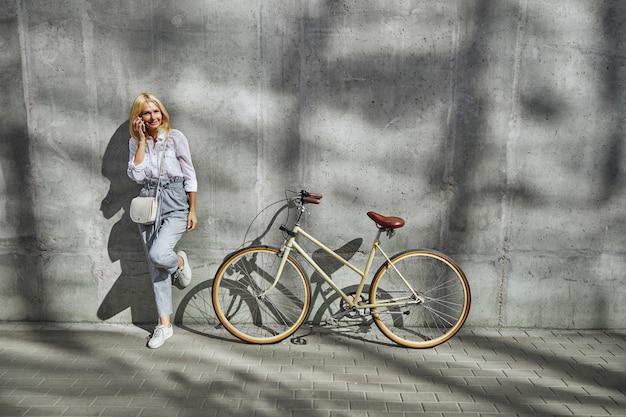 야외의 회색 벽에 격리된 자전거 근처에 서서 친구들과 휴대전화로 통화하는 매력적인 여성