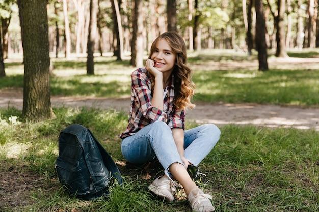 배낭 공원에서 포즈 매력적인 여성 관광객. 미소로 잔디에 앉아 놀라운 곱슬 소녀의 야외 촬영.