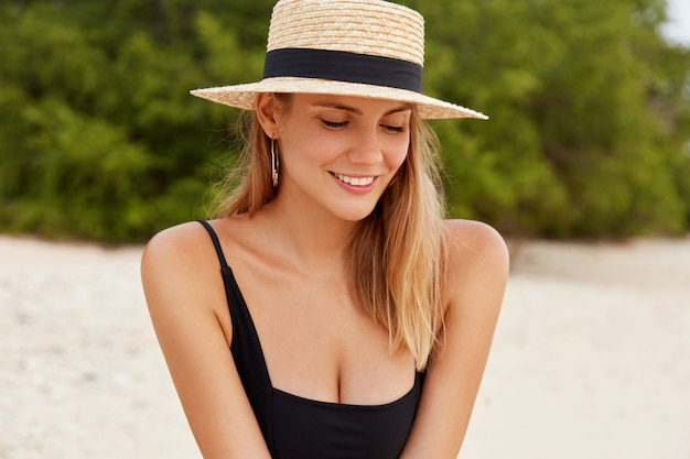 Charming female tourists in fashionable hat looks shyness down, smiles joyfully, wears bathing suit, rests after active walk or swimming in ocean,