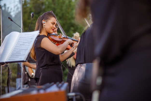 Charming female violinist playing in orchestra on the street