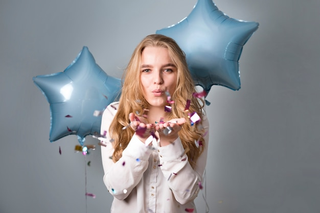 Charming female with balloons blowing at confetti