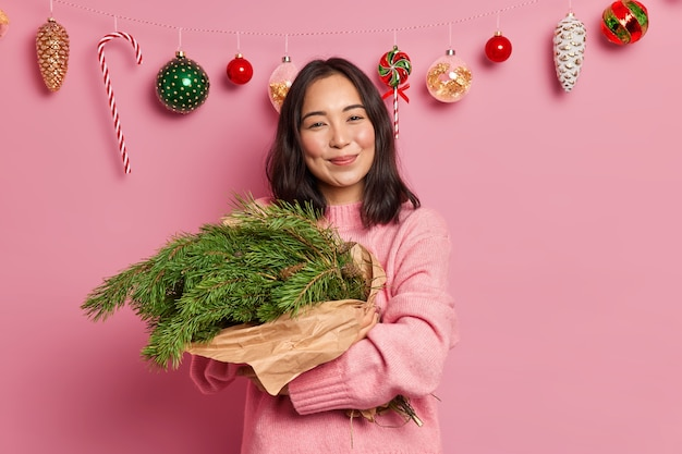 Charming female with dark hair and pleasant smile embraces fir tree branches arranged in bouquet has festive mood wears casual sweater