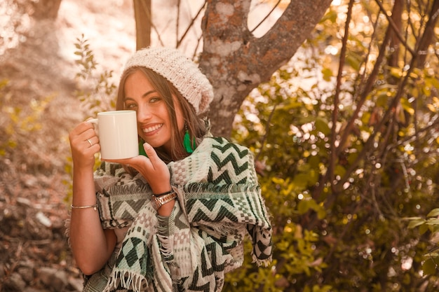 Charming female with mug in forest