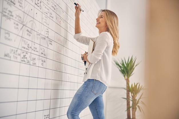 Очаровательная работница пишет на доске планировщика и улыбается, держа в руках альбом