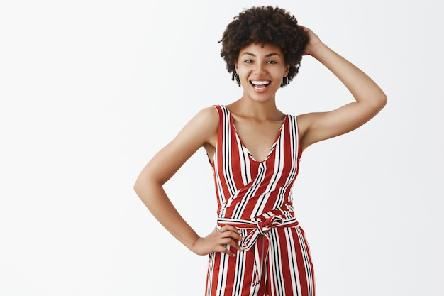 Charming feminine and flirty gorgeous african american female with curly hairstyle in trendy striped overalls holding hand behind head and arm on waist, smiling joyfully posing over gray wall