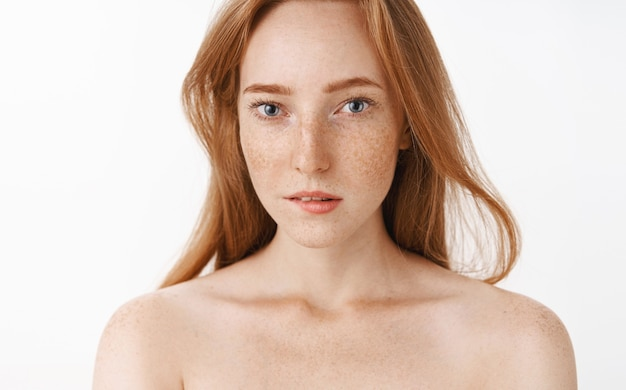 Charming feminine redhead young woman with freckles and beautiful blue eyes biting lower lip from desire and interest turning attention at intriguing thing standing naked