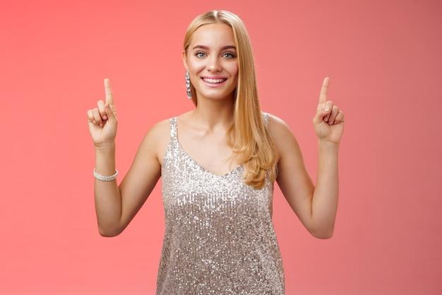 Affascinante donna bionda tenera femminile in abito da festa d'argento alza le mani puntando verso l'alto sorridendo contentissima consiglia cosmetici fantastici un buon servizio di prodotto, in piedi felicemente sorridendo sfondo rosso.