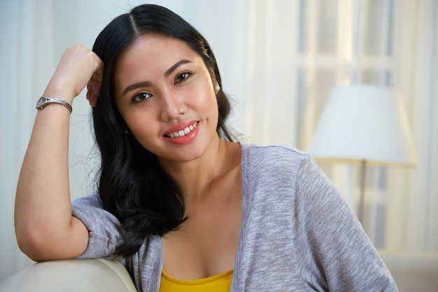 Charming filipino woman leaning on sofa back