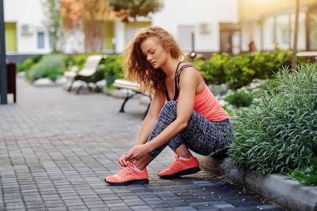 沿道に座って靴ひもを結ぶスポーツウェアに身を包んだ魅力的なフィットの白人女性。