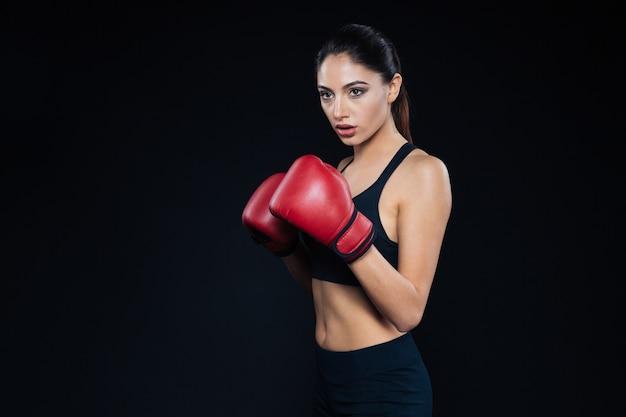 黒の背景のボクシンググローブに立っている魅力的なフィットネス女性
