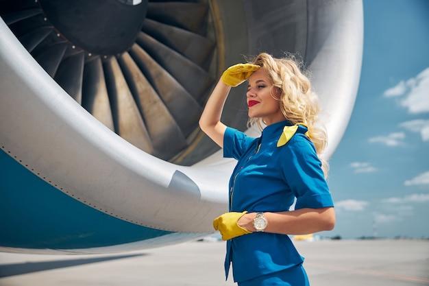 Очаровательный бортпроводник в синей форме смотрит в сторону и улыбается, прикрывая глаза от солнца рукой