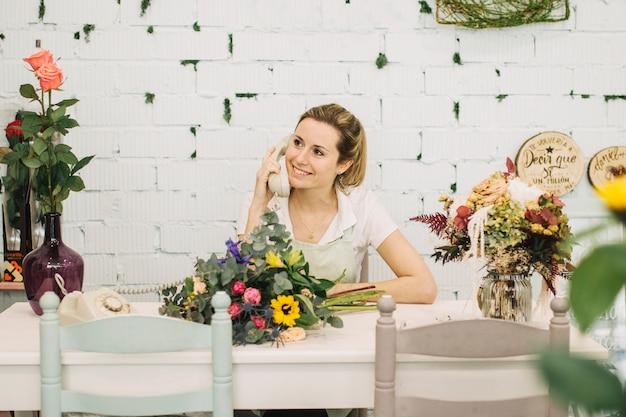 テーブルで電話で話す魅力的な花屋