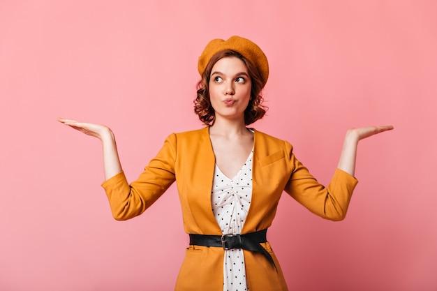肩をすくめるジェスチャーを示す魅力的なフランスの若い女性。手を上げてポーズをとる黄色い服を着た白人の女の子のスタジオショット。