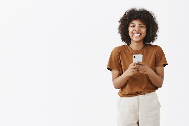 Charming and friendly african american teenage girl with curly hair in stylish outfit holding smartphone and smiling broadly
