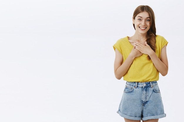 Charming friendly and cute adult tall girl in yellow t-shirt and shorts holding palms on chest and smiling feeling thankful and grateful