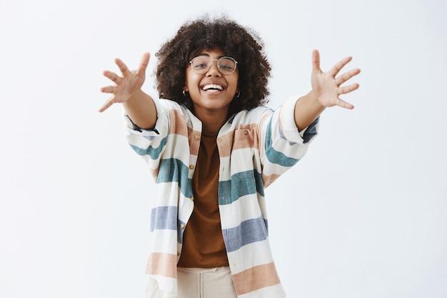 Affascinante donna moderna afroamericana amichevole e carina in abito elegante tirando le mani verso per dare abbraccio