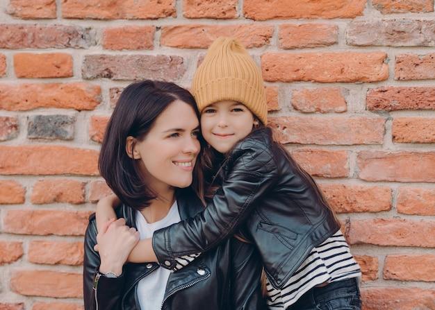매력적인 친절한 어린 아이와 그녀의 어머니는 검은 가죽 자켓을 입고 서로를 포옹합니다.