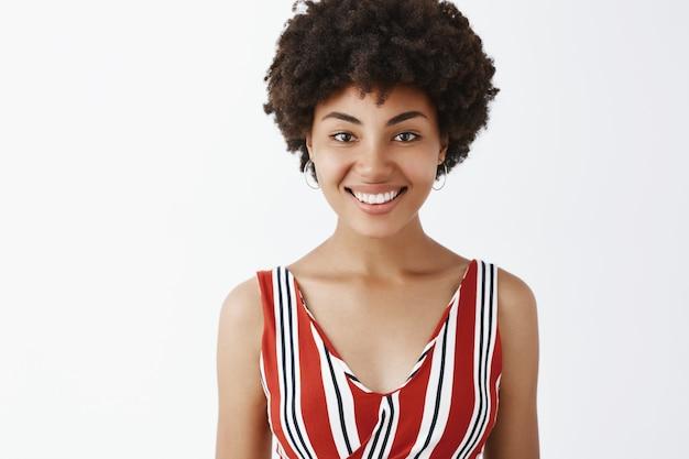 Очаровательная дружелюбная афроамериканка в полосатой блузке радостно улыбается и смотрит вежливо и беззаботно.