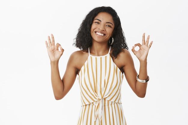 魅力的なフレンドリーな外観の浅黒い肌の女性で、幸せと喜びから微笑んでいる巻き毛の髪型で、大丈夫または優れたジェスチャーを示す頭を傾けます