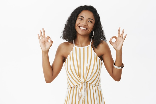 Charming friendly-looking dark-skinned female with curly hairstyle smiling from happiness and joy tilting head showing okay or excellent gesture
