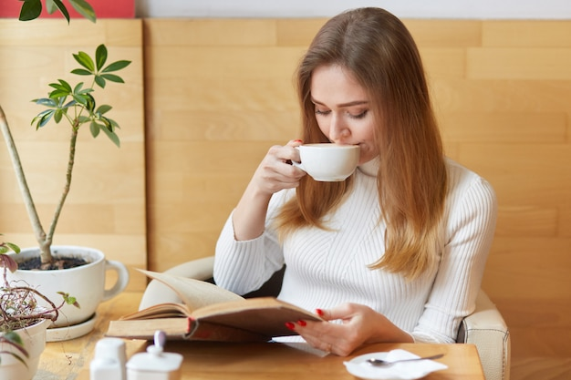 Charming fun-loving girl takes sips of tea, reads action packed book, focuses all attention on plot. young model sits near green plants and hot coffee on table.
