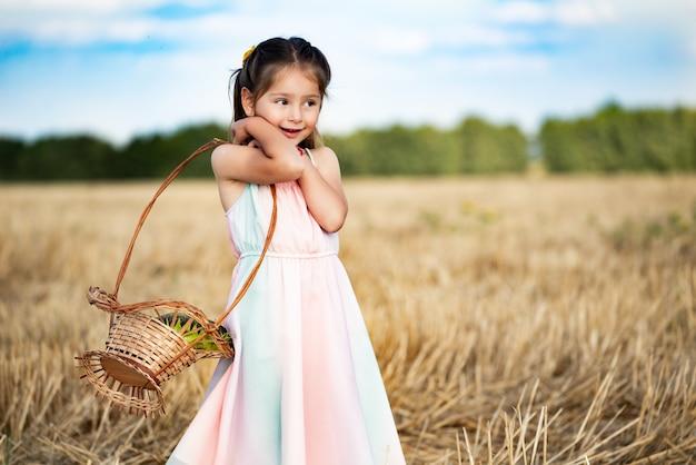 긴 드레스를 입은 매력적인 펑키 다섯 살짜리 소녀가 손에 고리 버들 바구니를 들고 경 사진 밀을 들고 밭을 걷고 있습니다. 수확과 가을 개념