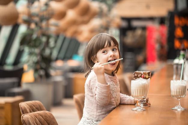 Очаровательная смешная маленькая девочка пьет молочный коктейль
