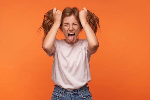 Affascinante donna rossa divertente in maglietta bianca e blue jeans, guardando e mostrando la lingua, divertendosi