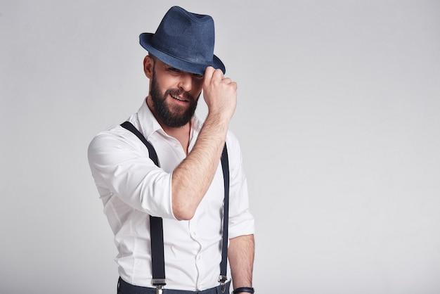 Очаровательный гангстер. красивый молодой человек в подтяжках поправляет шляпу и смотрит в камеру с улыбкой, стоя на сером фоне