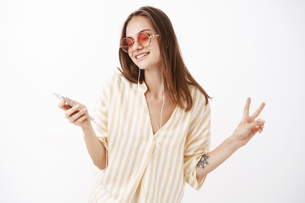 Очаровательная нежная европейская женщина в солнцезащитных очках и стильной желтой блузке слушает музыку в наушниках и держит смартфон, танцует, демонстрируя жест мира, наслаждаясь звуком