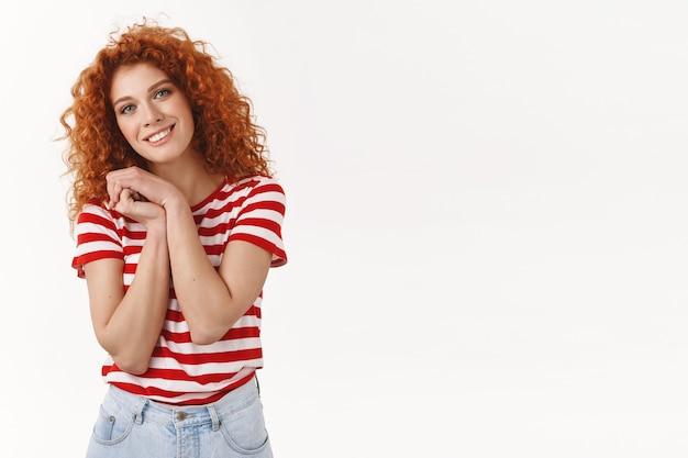 魅力的な優しい赤毛の巻き毛の女の子25代の青い目は手のひらを押します胸の甘い素敵なシーン笑顔感謝の気持ちを傾ける頭は素晴らしい贈り物、白い壁に感謝します