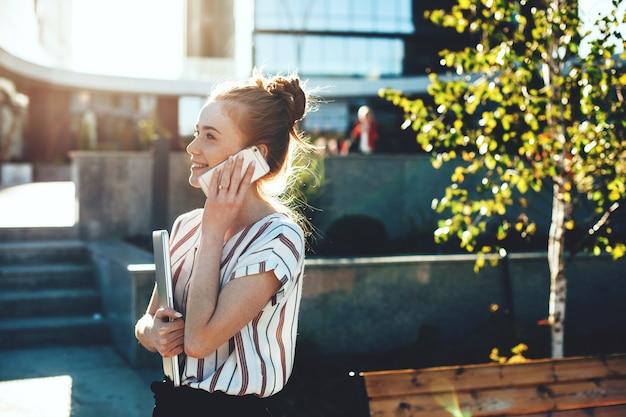 魅力的な生姜白人起業家は、誰かと電話で話している間、彼女のラップトップを持っています