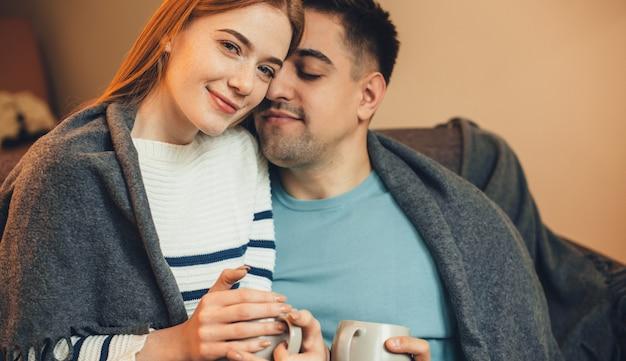 彼女のボーイフレンドと一緒にソファに横たわって、一緒にお茶を飲んでいる赤い髪の魅力的な生姜白人女性