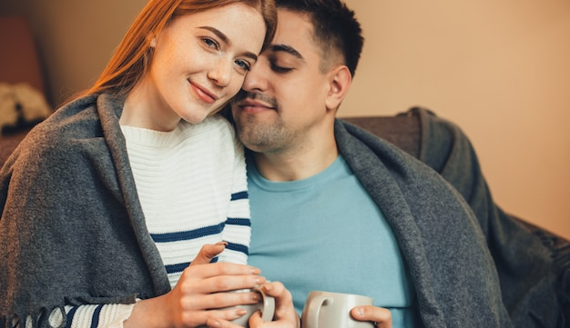 Charming ginger caucasian woman with red hair lying on the sofa with her boyfriend and having a tea together