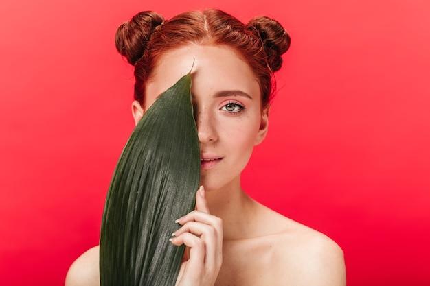 緑の葉でポーズをとる魅力的な生姜の女性。赤い背景に分離された植物を持つ魅力的な若い女性のスタジオショット。
