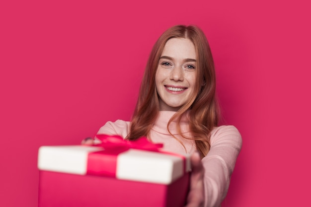 Charming ginger woman with freckles is giving a present at the camera smiling on a pink wall at studio