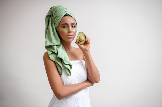 アボカドでポーズをとっている彼女の目の下のパッチでシャワーを浴びた後の魅力的な女の子