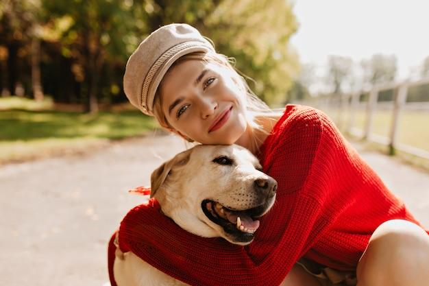 秋の公園で楽しい時間を過ごしている魅力的な女の子と彼女の犬。美しい犬のポーズで素敵なブロンド。