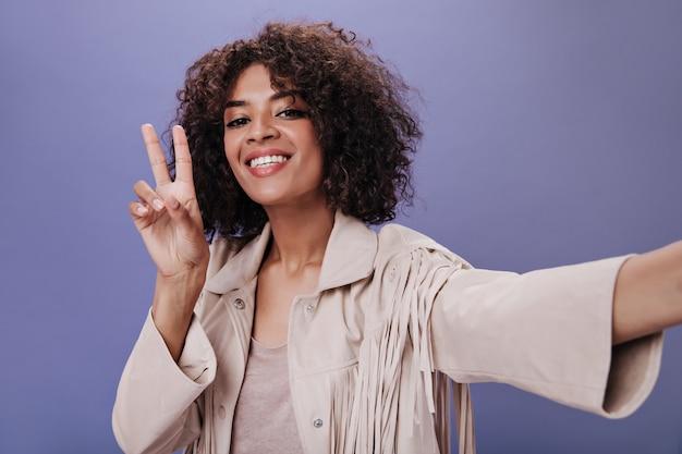 Affascinante ragazza in abito beige sorride, prende selfie e mostra segno di pace