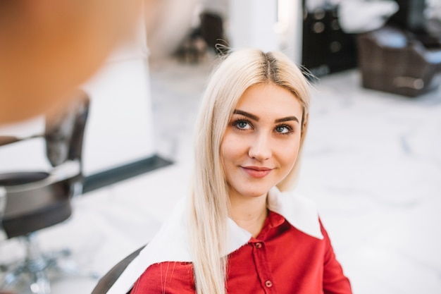 Charming girl in chair of hairdresser